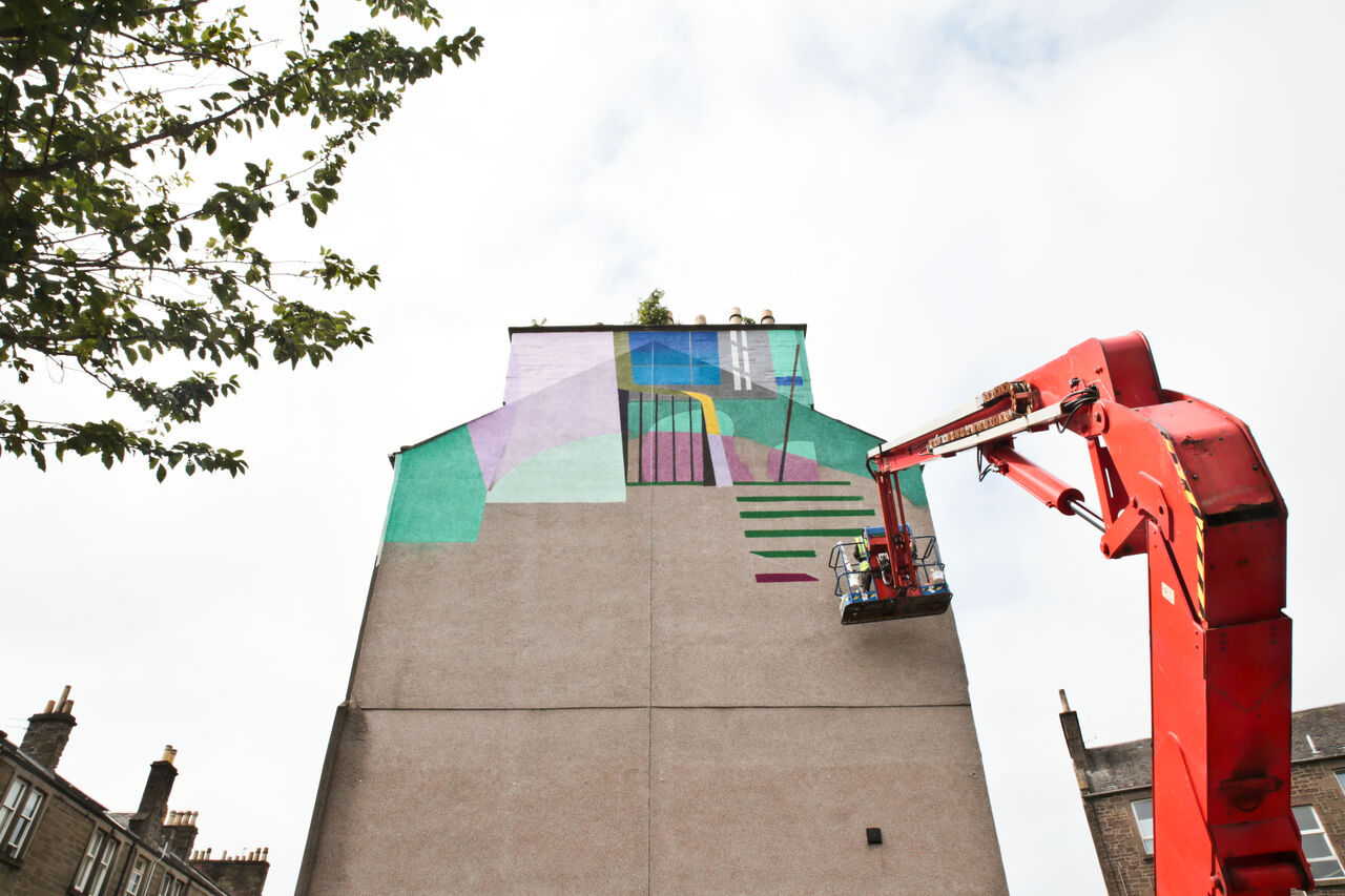 A large gable end mural in Dundee. It's colourful and shows the interior of a home, with a focus on a staircase and the outline of someone walking up it. This photo shows the mural in progress.