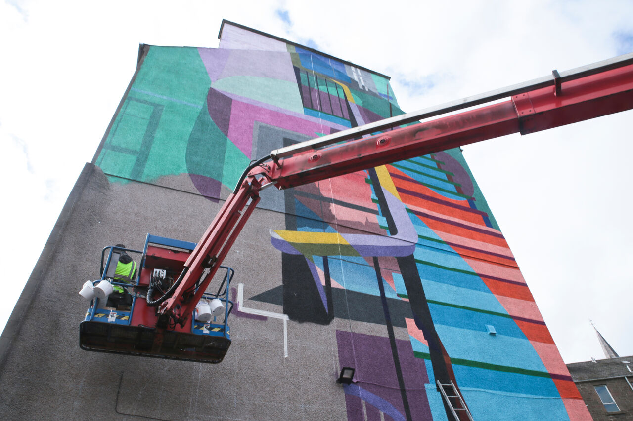 A large gable end mural in Dundee. It's colourful and shows the interior of a home, with a focus on a staircase and the outline of someone walking up it. This photo shows the mural in progress with the artists up in a cherry picker.