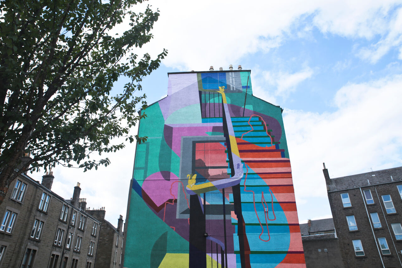 A large gable end mural in Dundee. It's colourful and shows the interior of a home, with a focus on a staircase and the outline of someone walking up it.