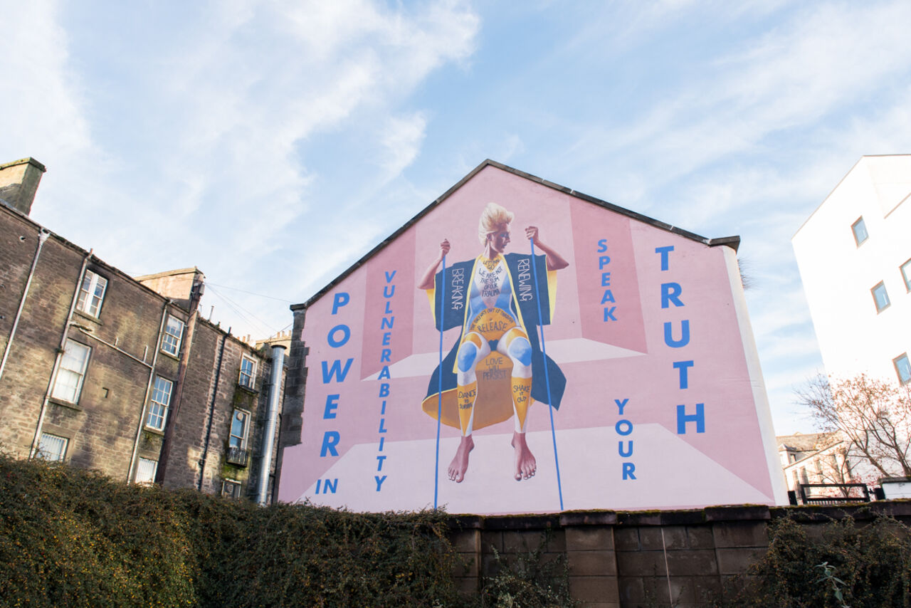 A large gable end mural in Dundee. It depicts a woman against a pale pink background, sitting down with words and phrases around here alluding to trauma, struggle and overcoming them.