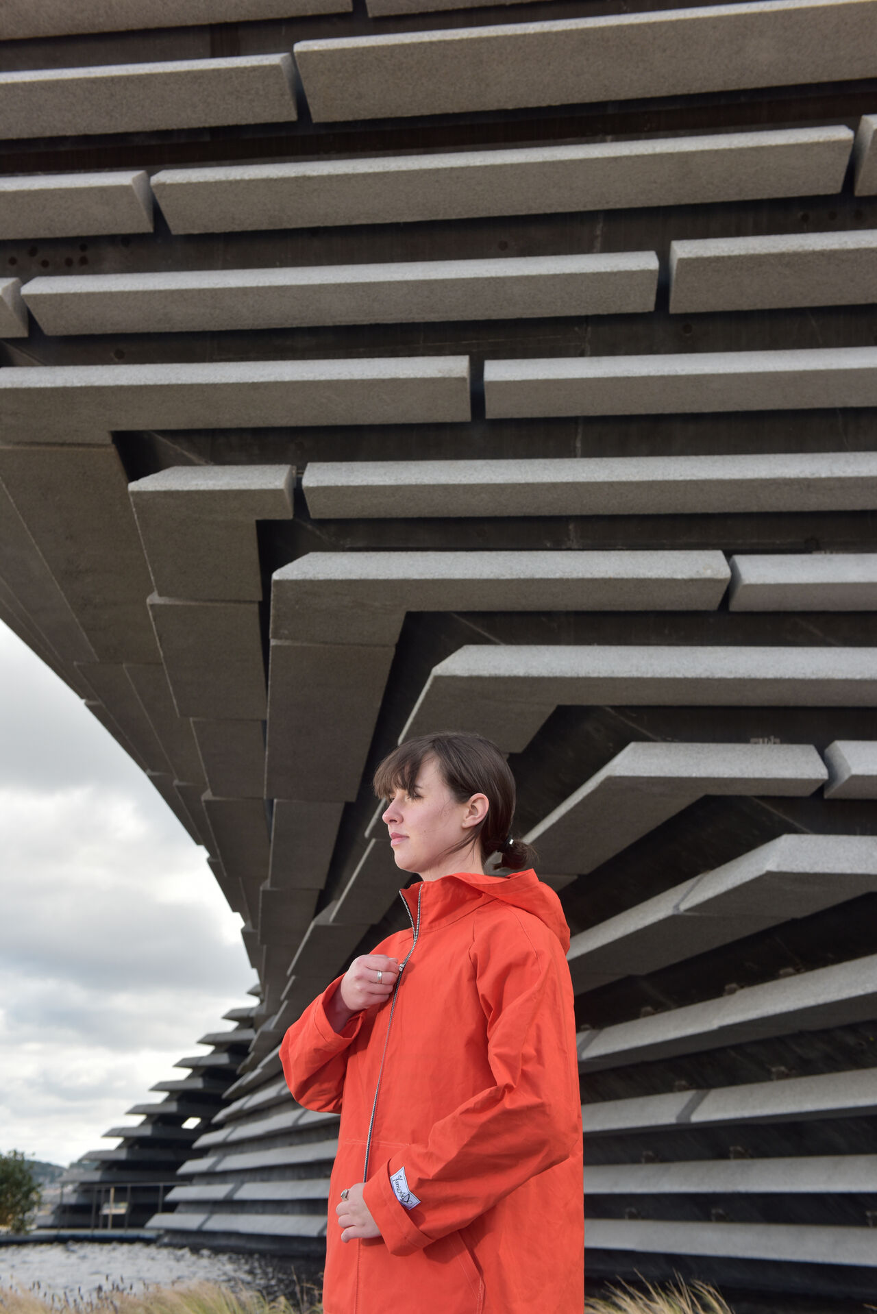 Someone posing outside V&A Dundee wearing an orange raincoat.