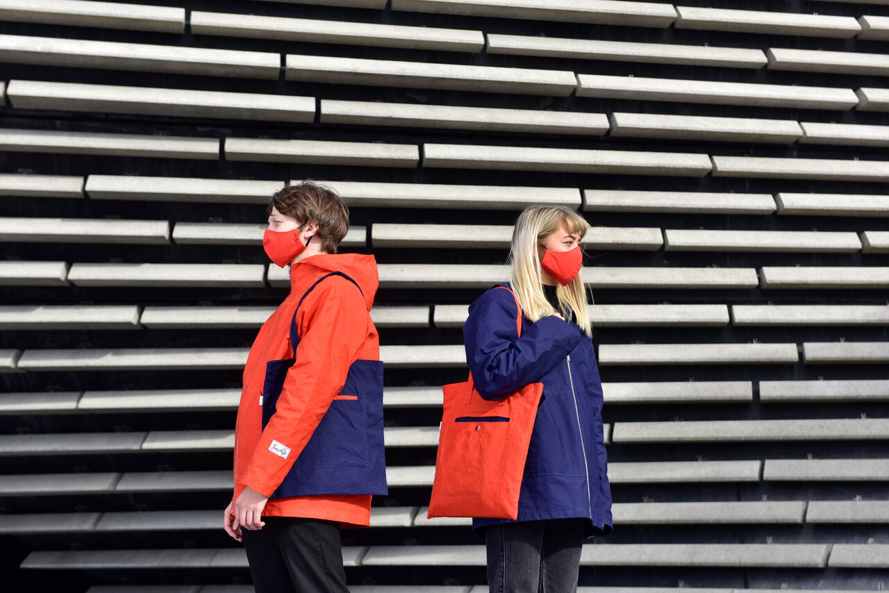 Two people posing in front of V&A Dundee wearing raincoats, one navy and one orange. They also have face coverings on and are holding tote bags made out of the same fabric as their coats.