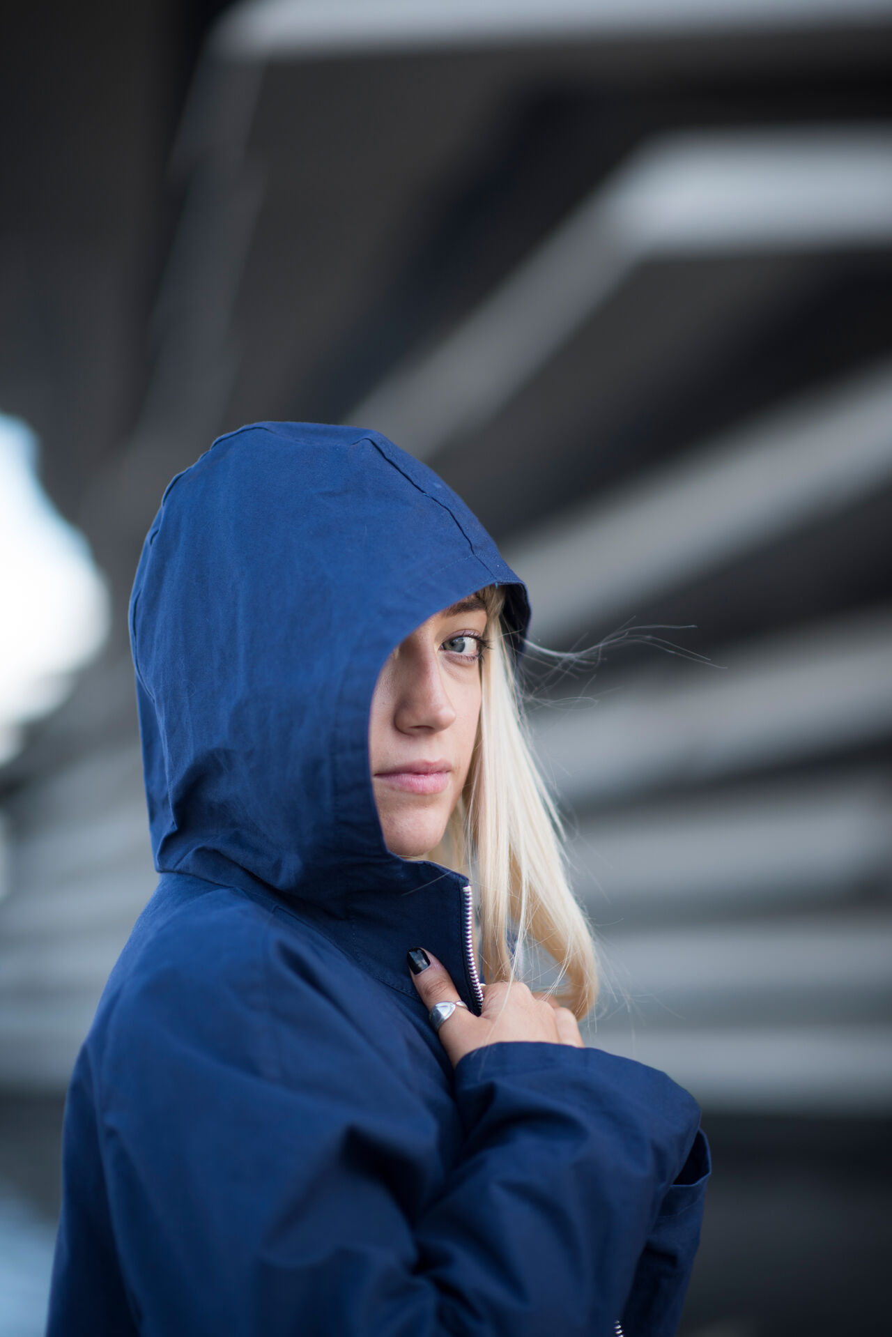 A person posing in front of V&A Dundee wearing a navy raincoat. She is side-on to the camera and has the hood up, looking sideways at the camera.