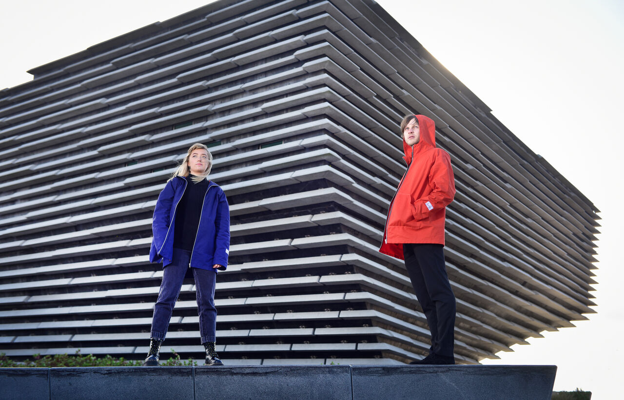 Two people posing in front of V&A Dundee wearing raincoats, one navy and one orange.