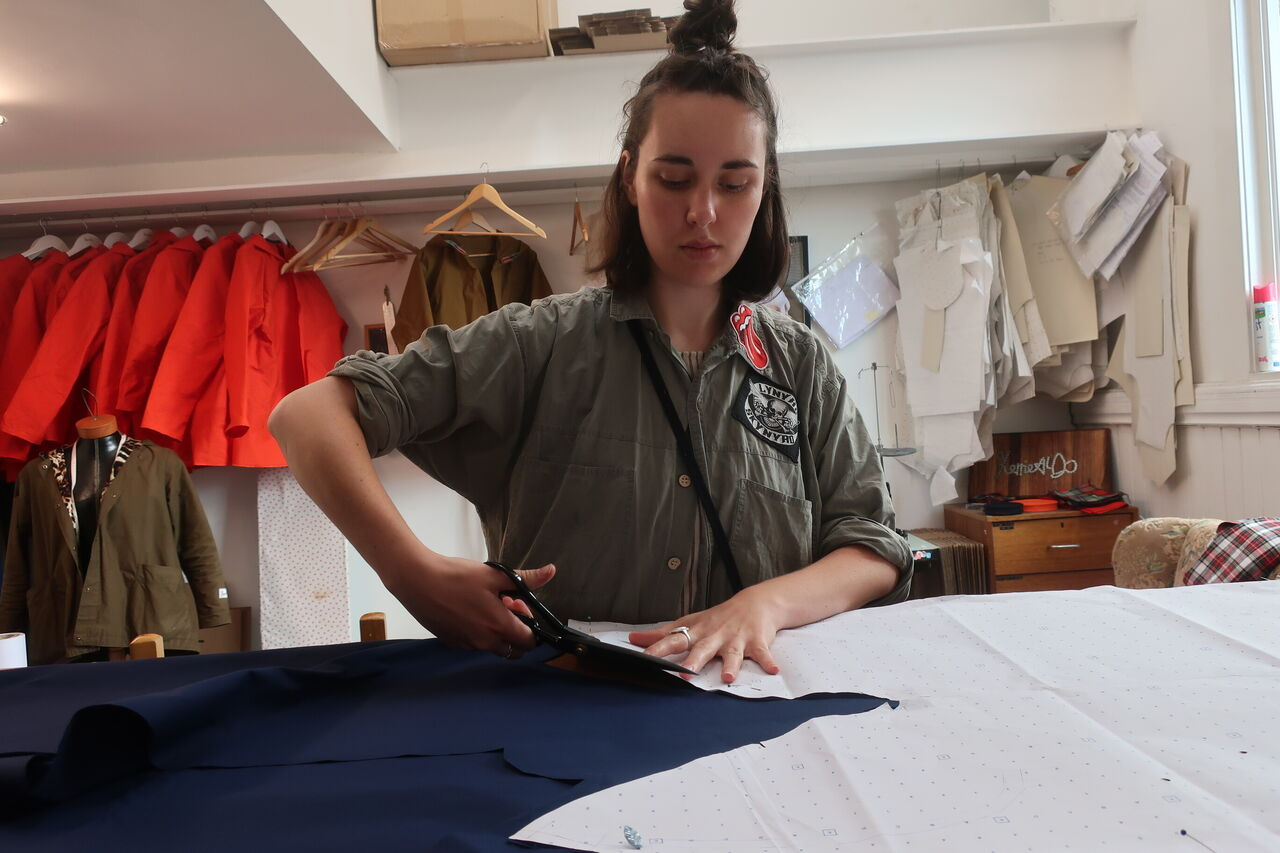 A woman is cutting out plain, navy fabric on a work table.