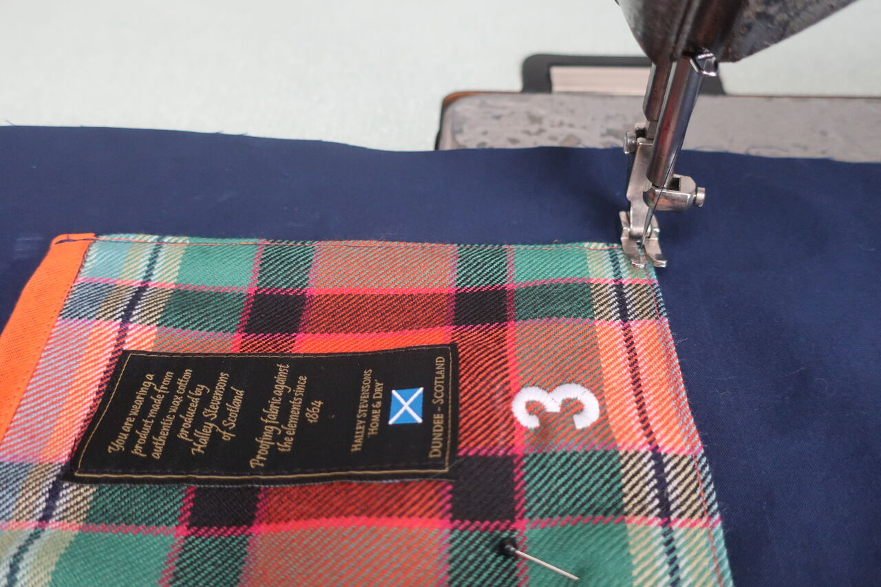 Close-up of a tartan patch being sewn into a navy raincoat.