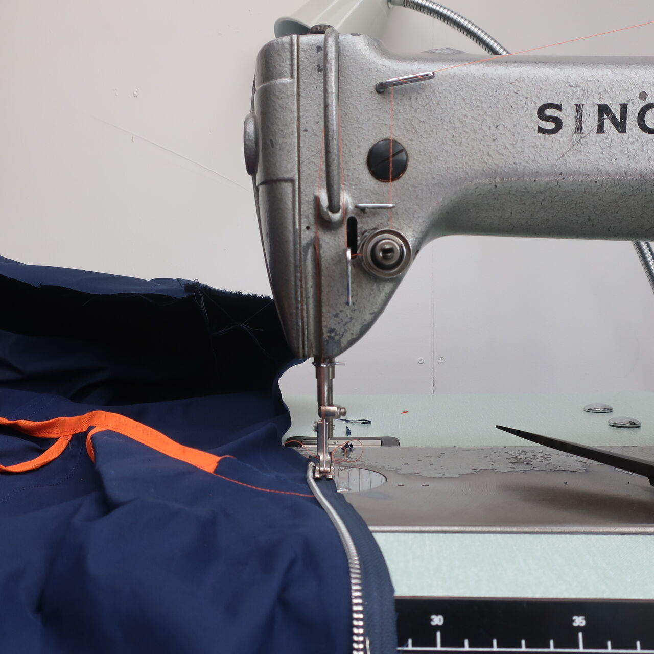 Close-up of a Singer sewing machine working on a navy raincoat.