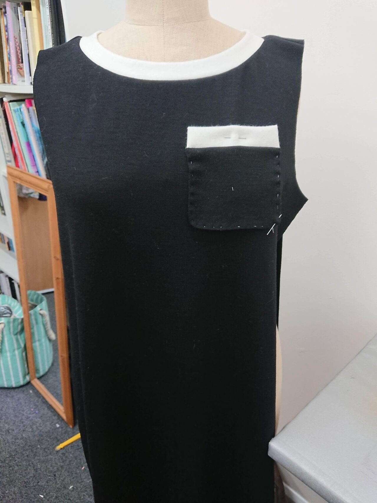 A black minidress hung on a mannequin in the process of being made.