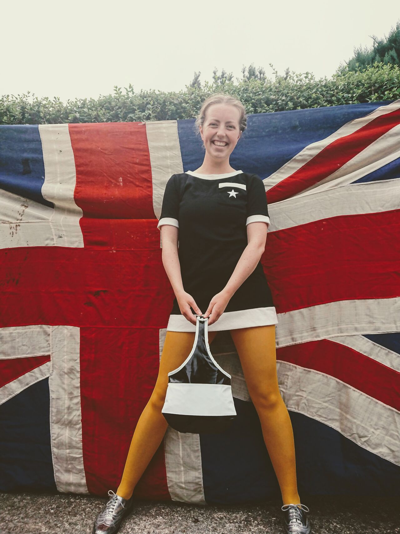 A model wears reproduction Quant attire in front of a union jack flag. The outfit is a black and white minidress and the model is holding a PVC handbag too.