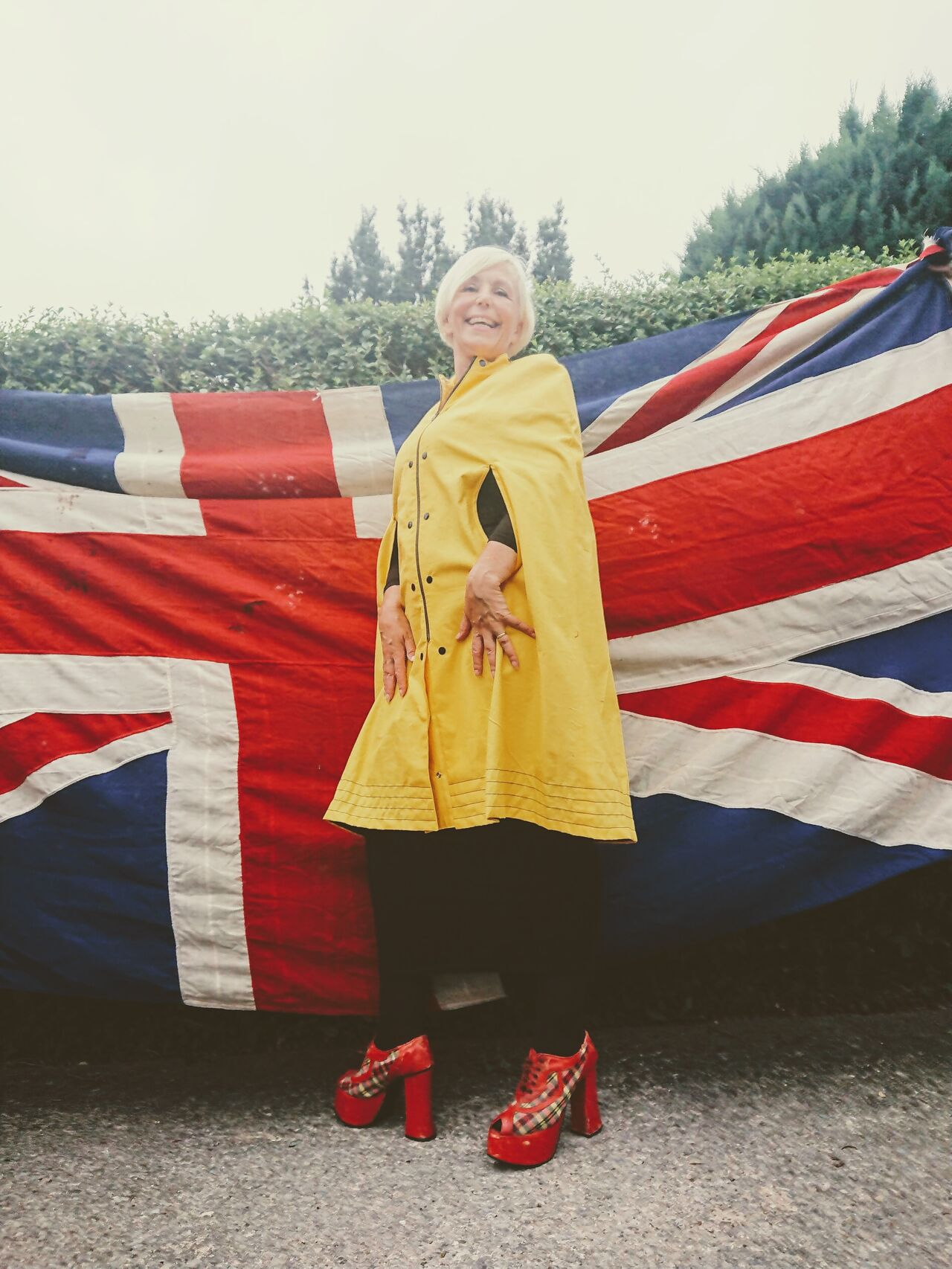 A woman wearing a reproduction Mary Quant cape poses in a garden in front of a union jack flag.