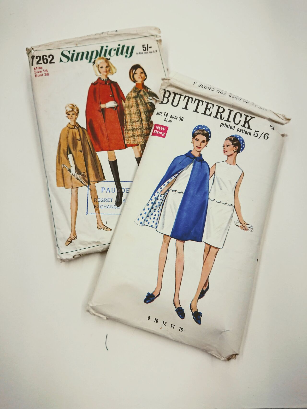 Two packs of Butterick sewing patterns with illustrations of capes on the front.
