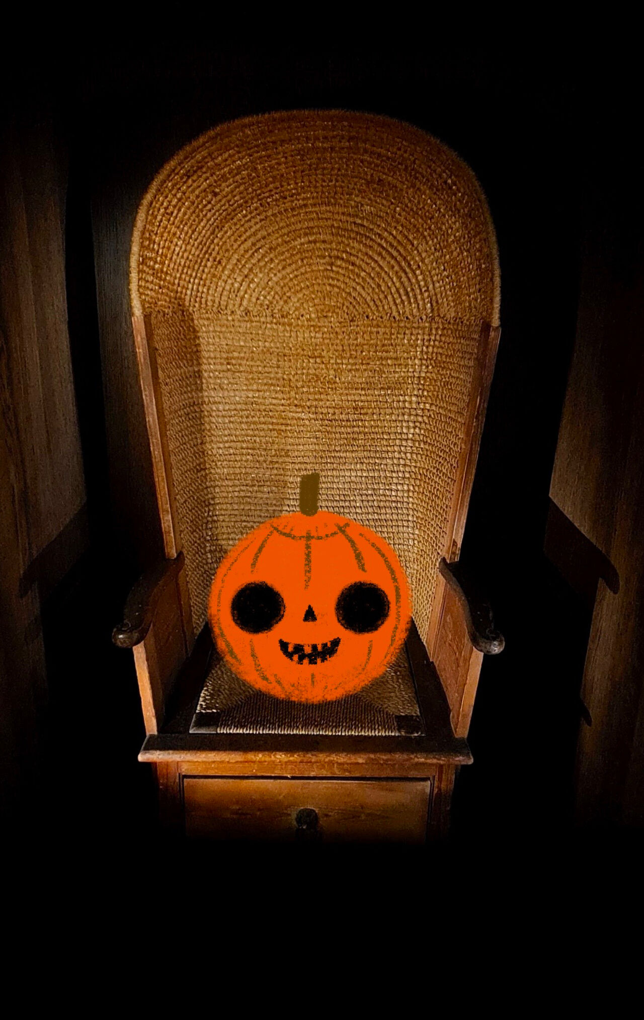 A photo of the Orkney chair in our galleries, but a bright orange illustrated pumpkin with a cheeky face sits on it.