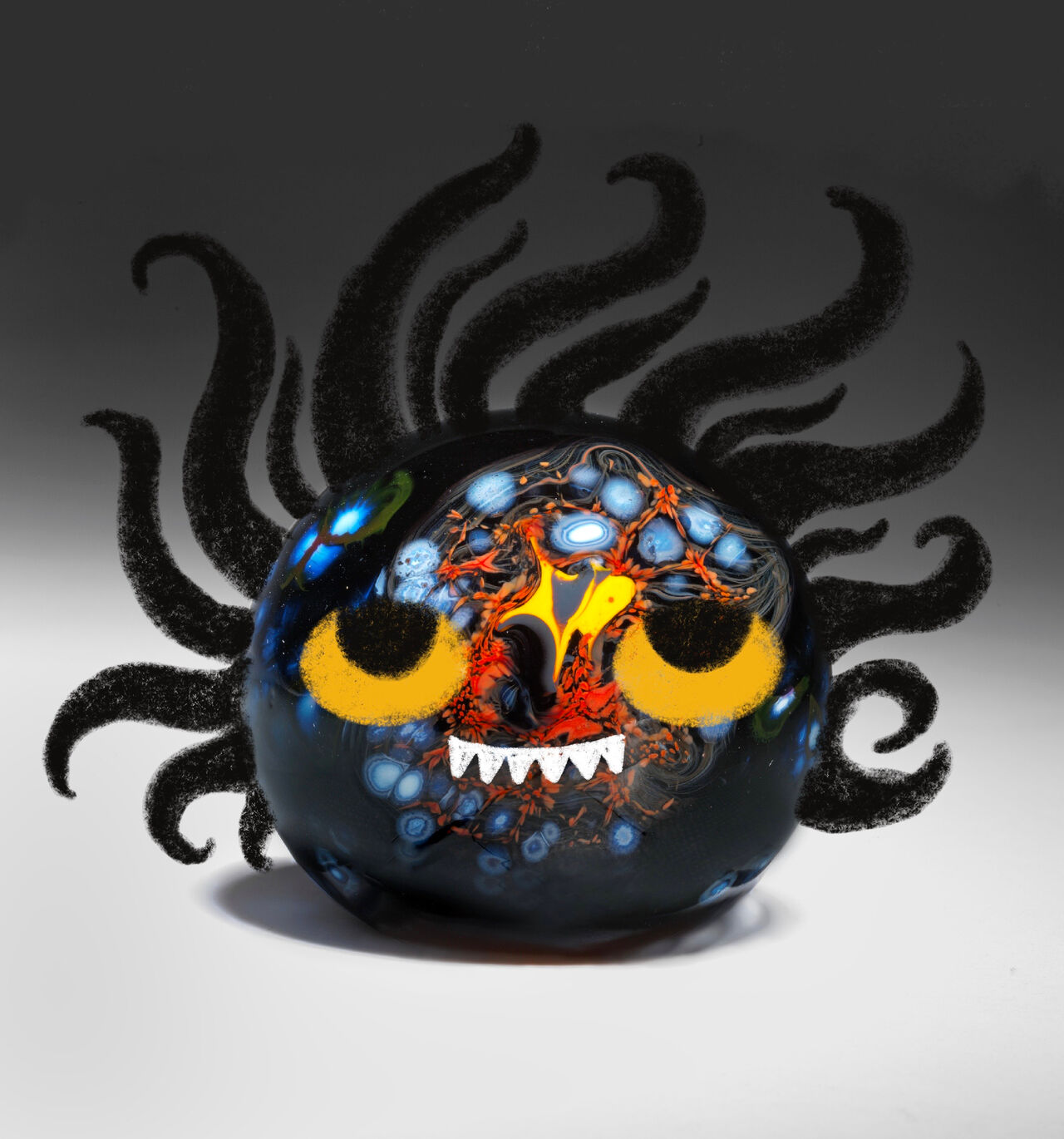 A photo of a glass paperweight with illustration over it to look like a wee monster.