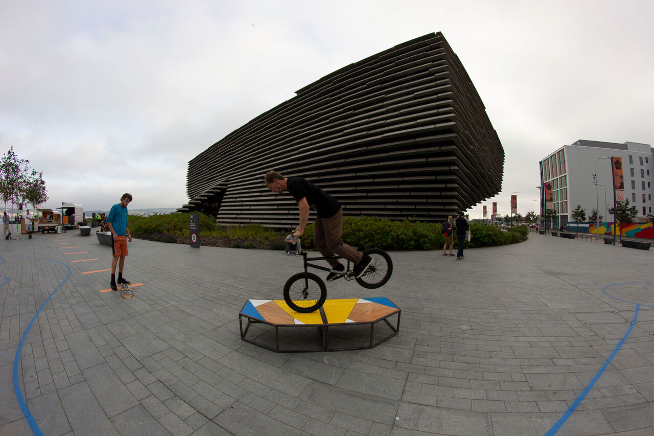 A BMX rider balancing their bike on the front wheel on the furniture next to the benches around V&A Dundee. The benches are plywood and yellow and blue.