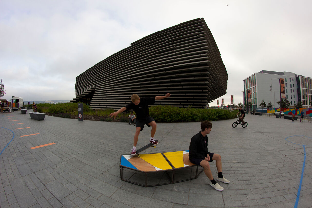 A skater doing a massive leap trick over the furniture next to the benches around V&A Dundee with someone sitting on the bench, relaxed. The benches are plywood and yellow and blue.