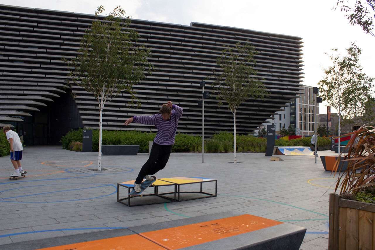 A skater doing a leap trick over the furniture next to the benches around V&A Dundee. The benches are plywood and yellow and blue.