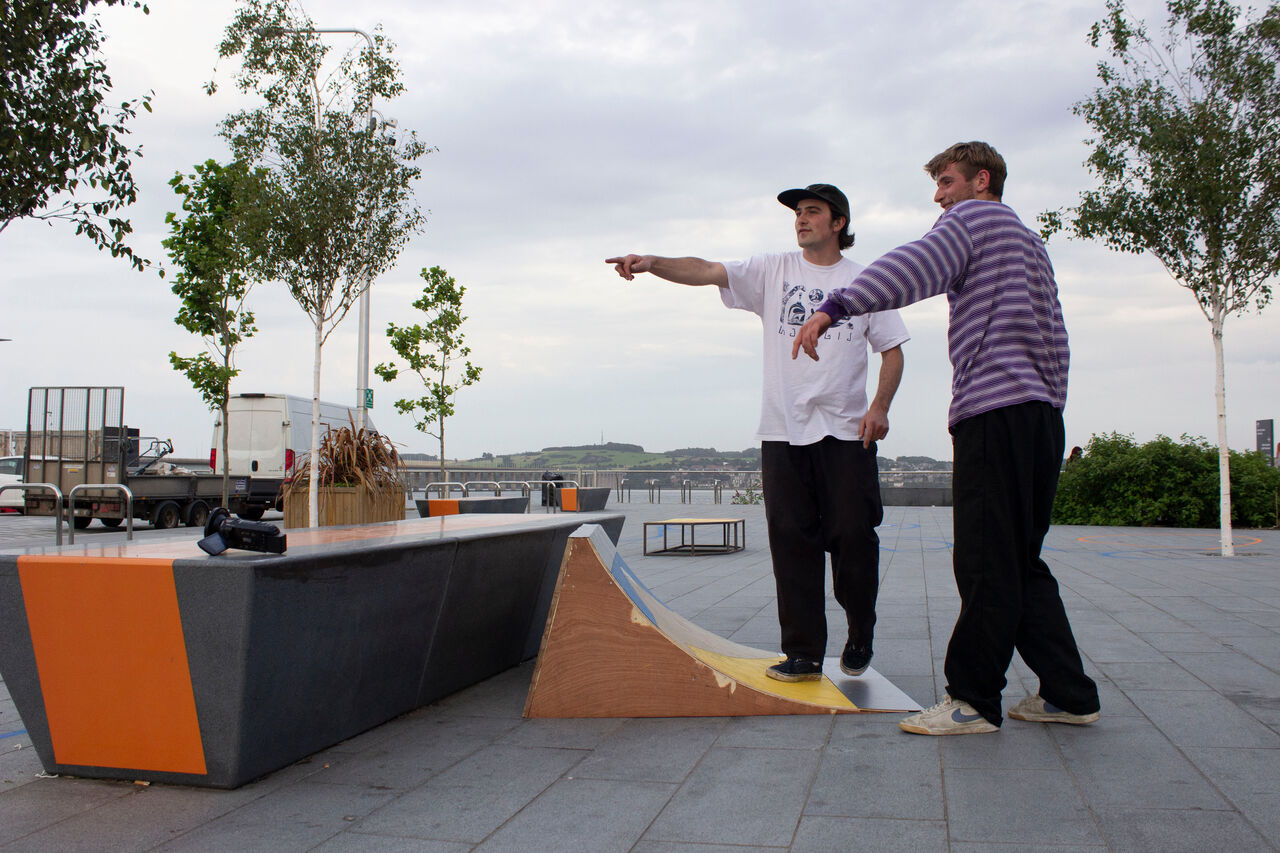 Photo of two people looking at a concrete bench and how it interacts with a portable wooden structure that skaters can use with the bench.