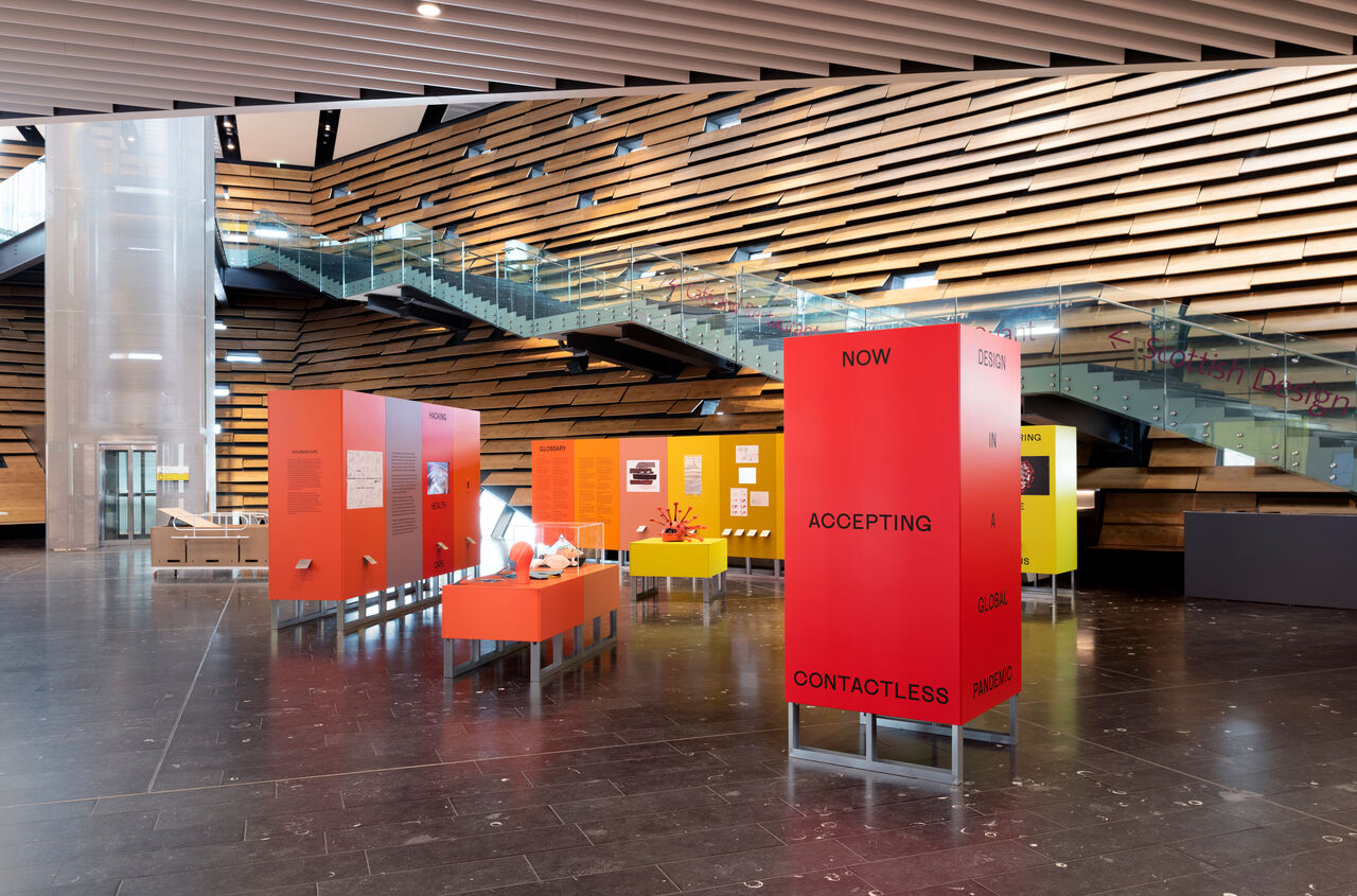 Now Accepting Contactless exhibition in the hall of V&A Dundee. Multicoloured panels and plinths form a deconstructed rainbow.