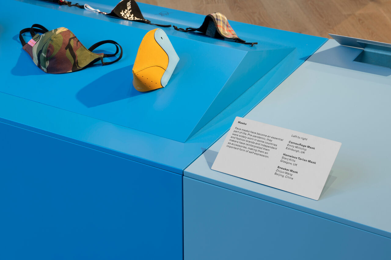Now Accepting Contactless exhibition in V&A Dundee. Close-up of blue plinths with face coverings on them.