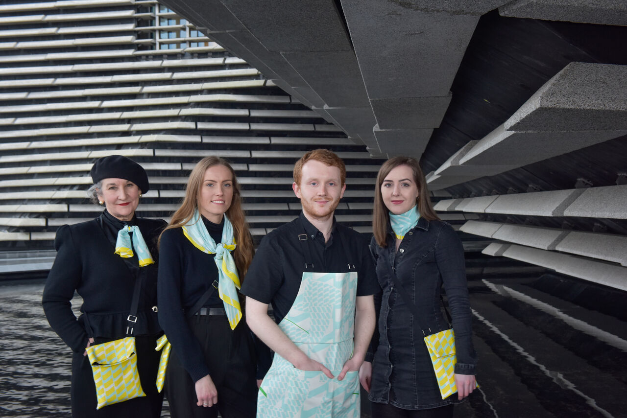 A group of people dressed mostly in black wearing scarves, aprons and bags in bright yellow and blue designs.