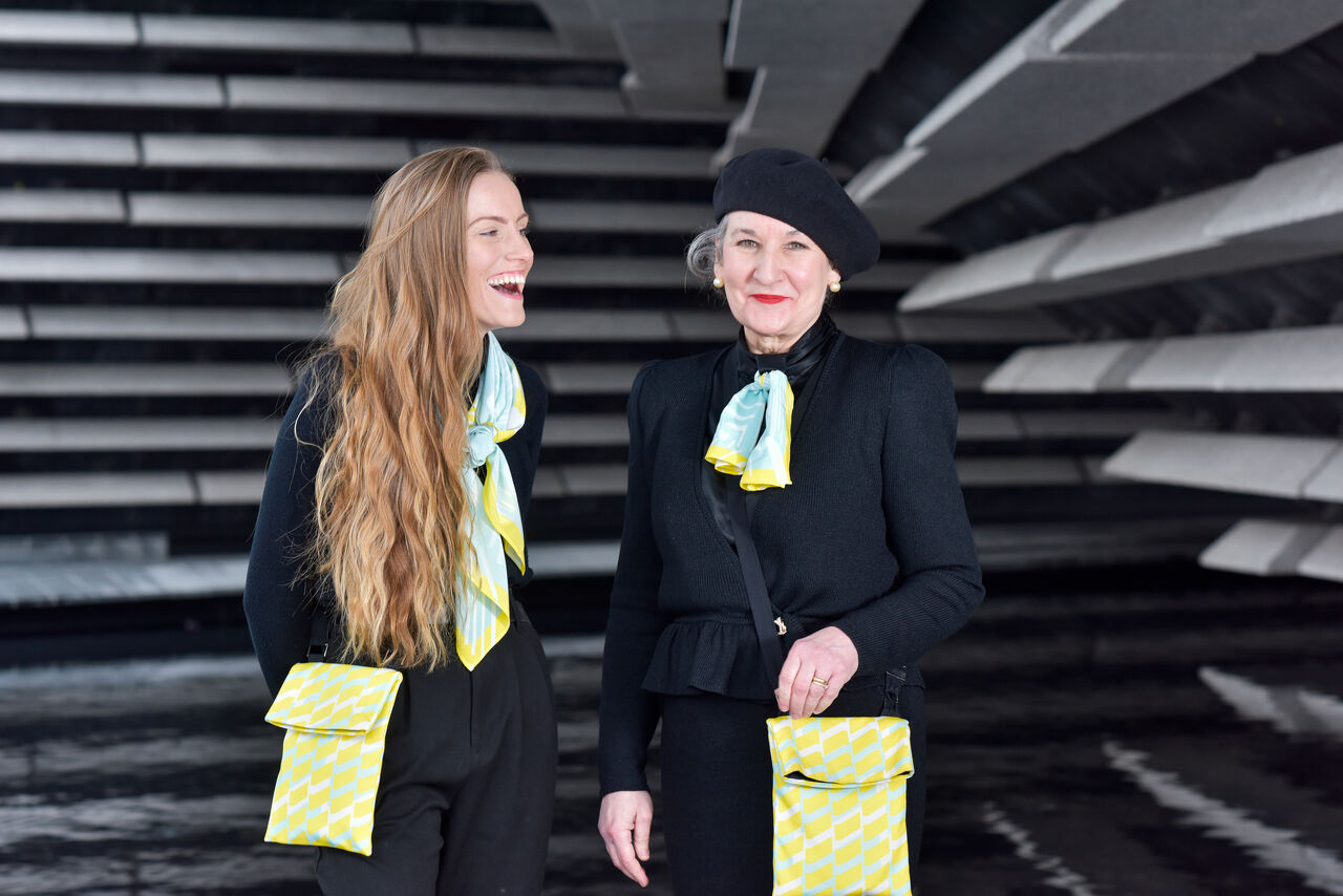 Two women laughing dressed mostly in black wearing scarves and bags in bright yellow and blue designs.