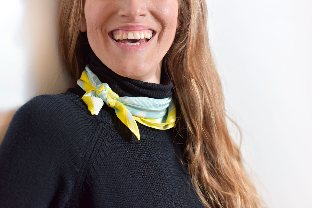 A woman mostly dressed in black posing against a plain background wearing a scarf in bright yellow and blue designs. The woman's face is just out of shot.