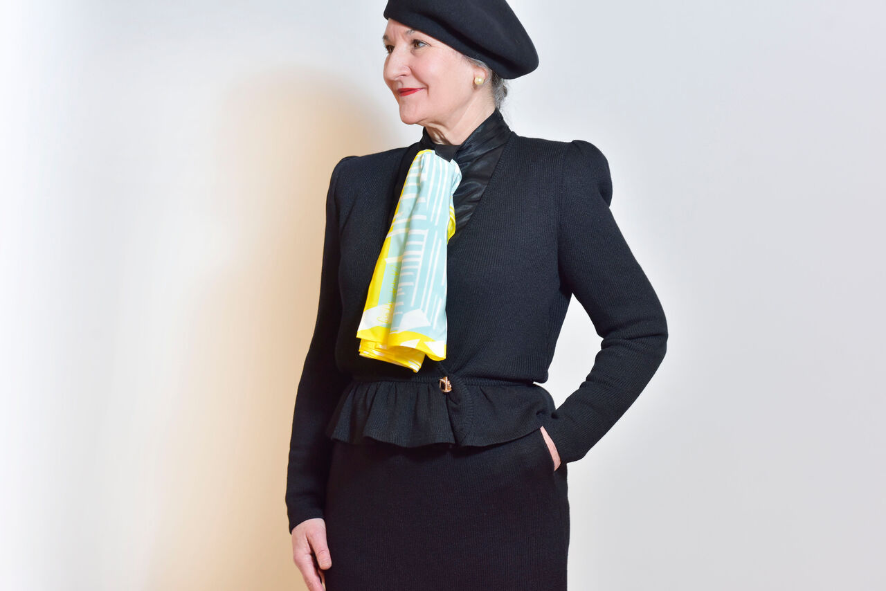 A woman mostly dressed in black posing against a plain background wearing a scarf in bright yellow and blue designs.