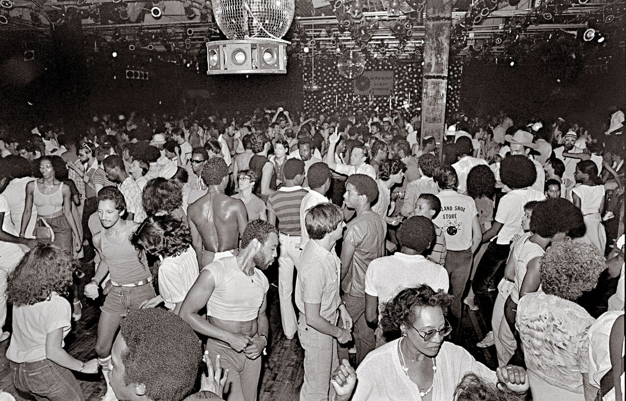 Black and white image of people dancing in a packed club