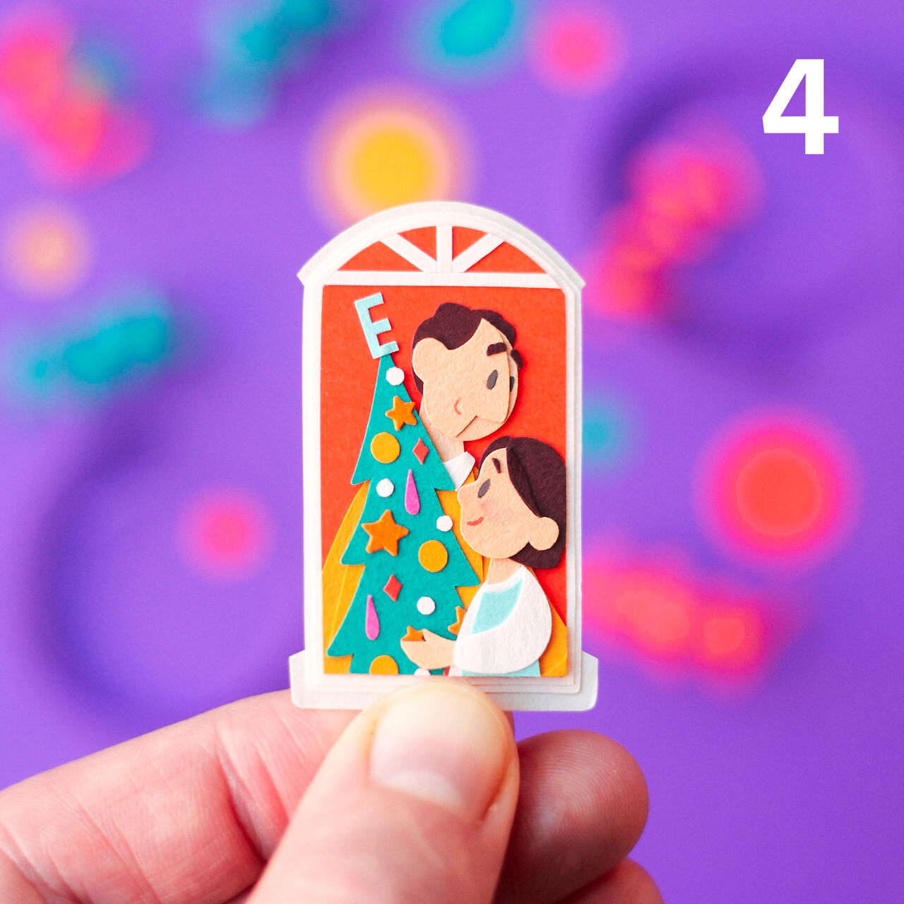 Fingers holding a tiny paper cut out illustration of a window.  A man and his daughter are decorating a Christmas tree.