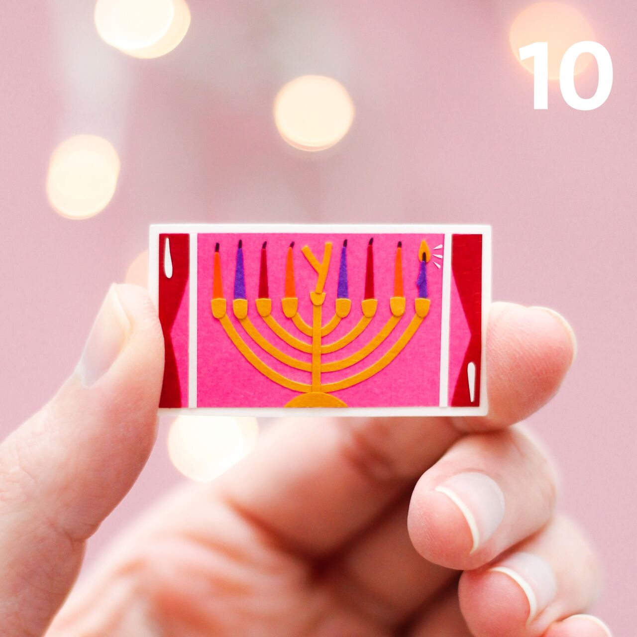 Fingers holding a tiny paper cut out illustration of a window. A menorah sits in the window.