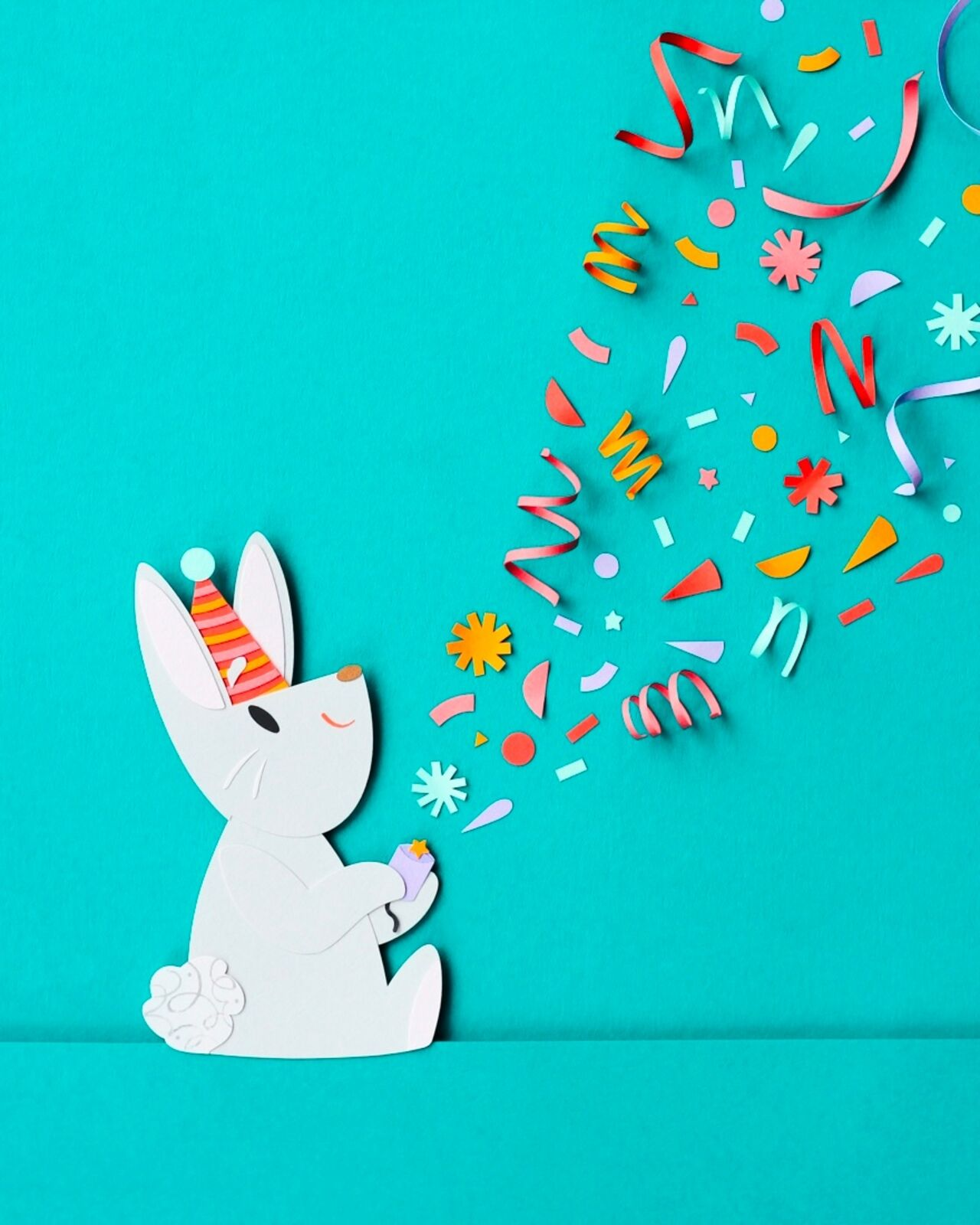 Photo of a wee white rabbit shooting a fun party popper, entirely made of paper cuttings.