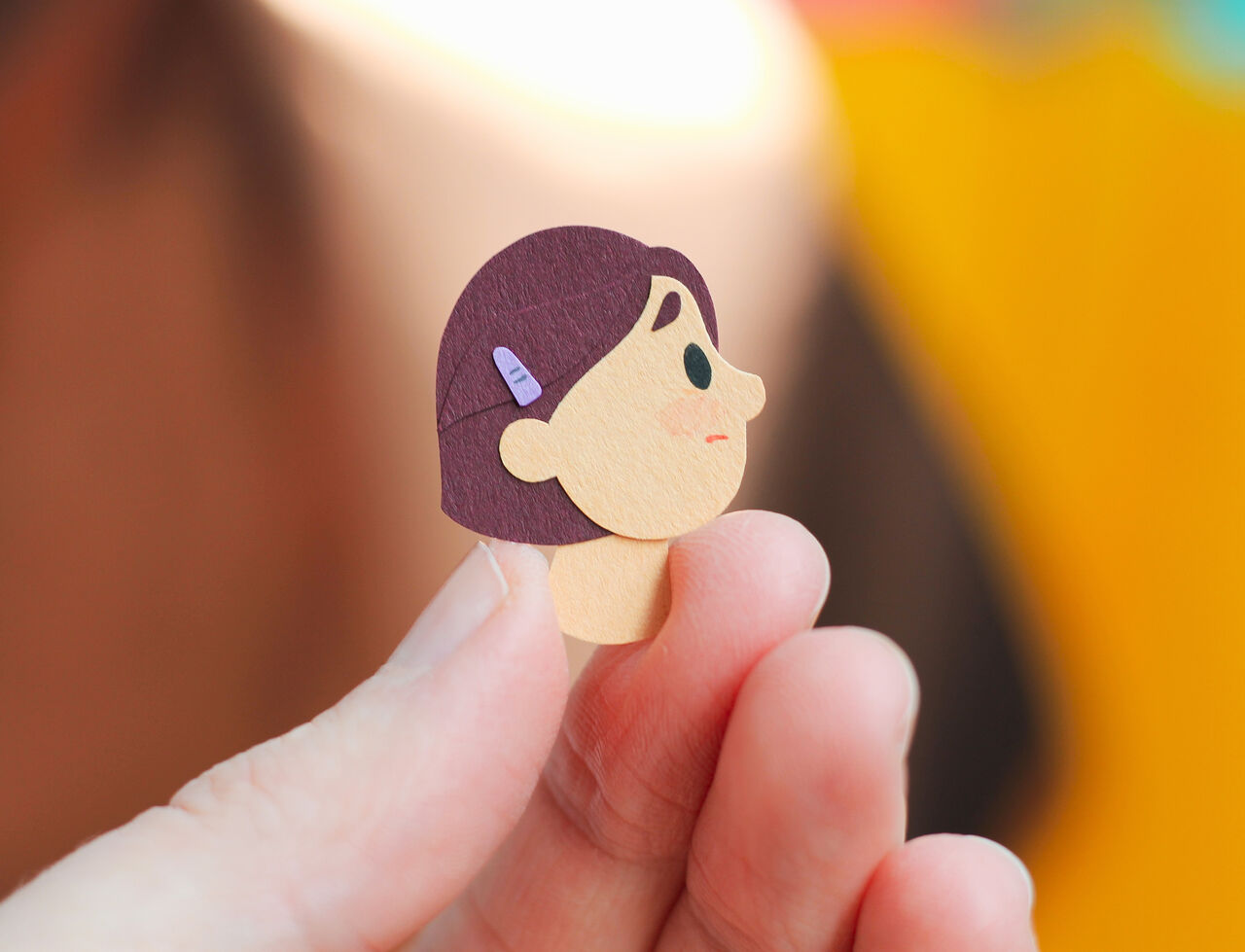 Close-up photo of someone's fingers holding a tiny head illustrated using cut paper.