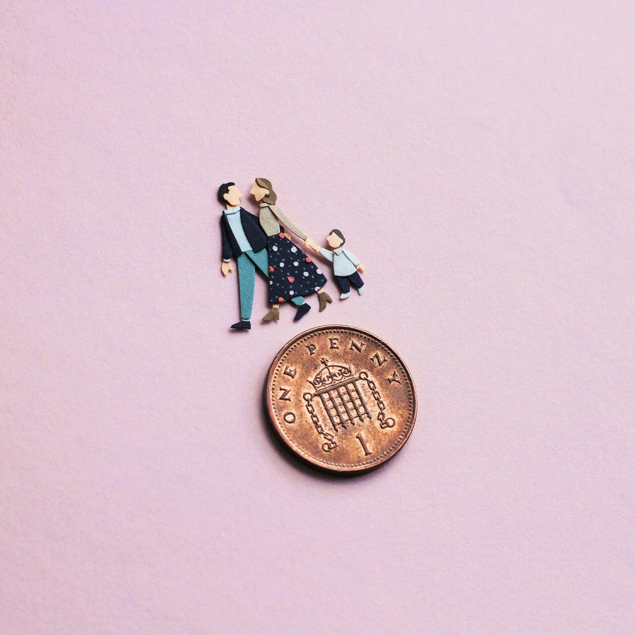 Photo of a hand holding tiny people made of cut paper, there's a man, woman and wee bairn.