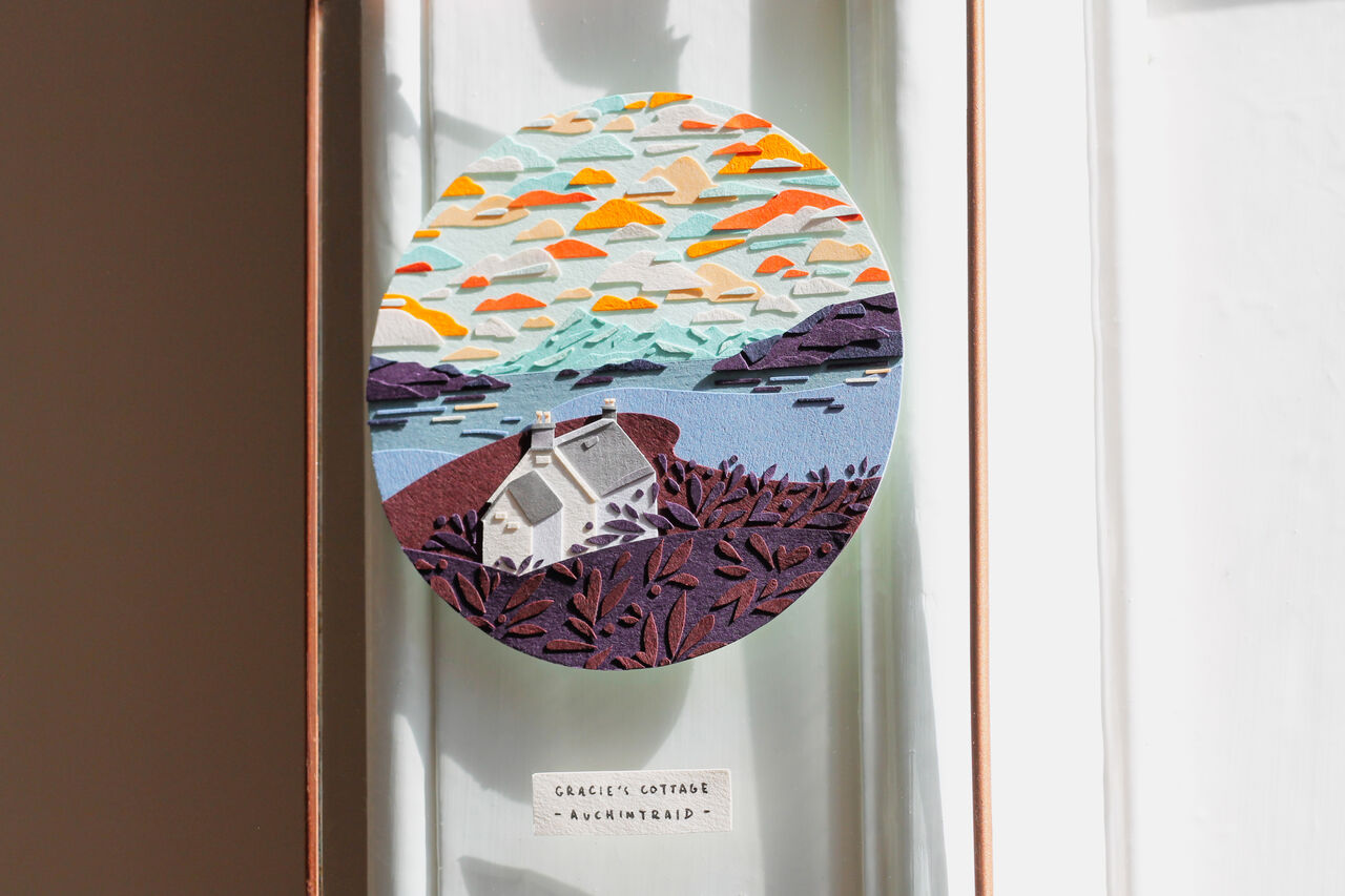 A hanging glass frame with a gorgeous Highland cottage scene depicted in cut paper.
