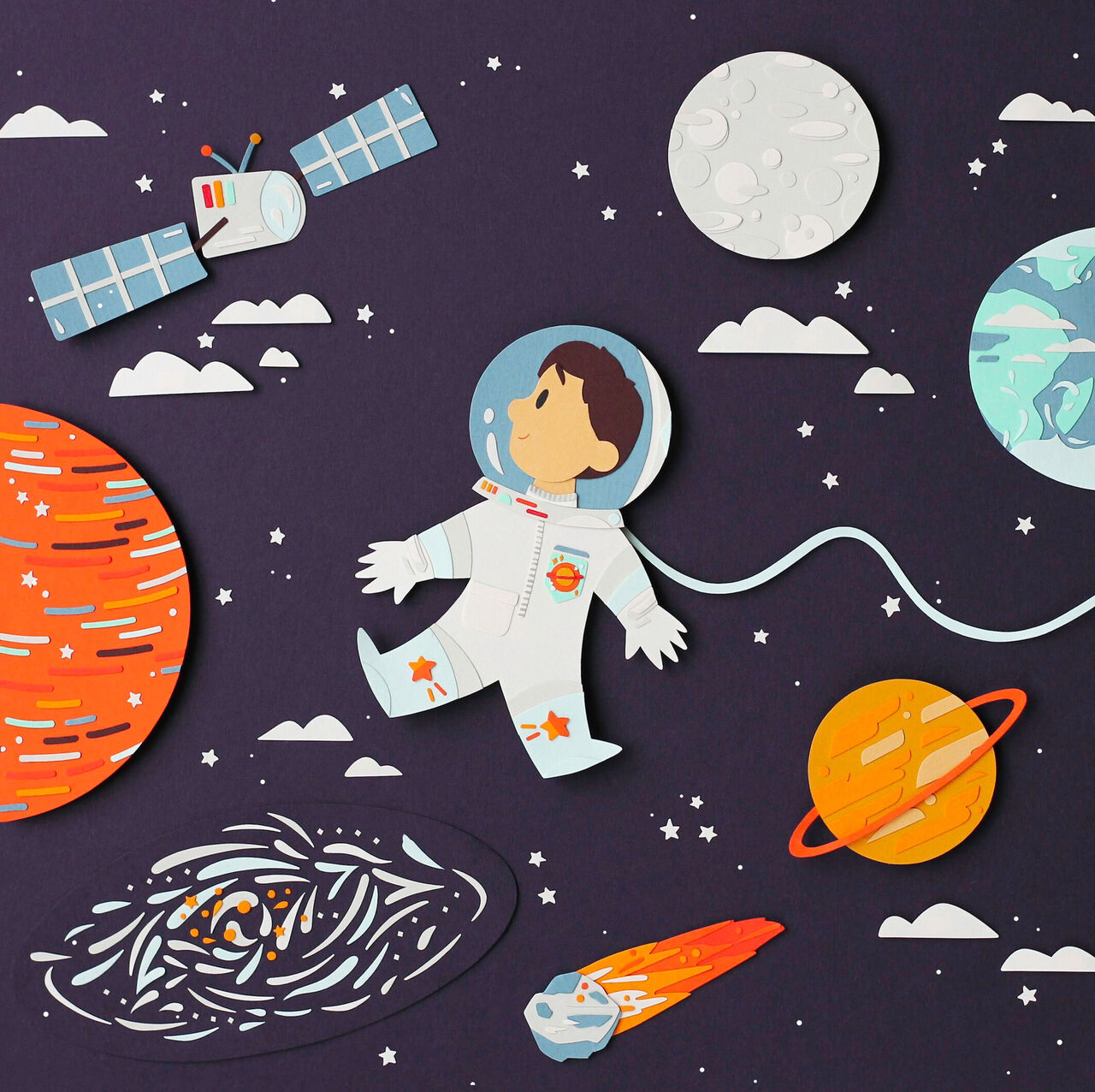 A beautifully illustrated scene of a lad floating in space in a spacesuit with planets and start around him. Entirely made out of paper cuttings!
