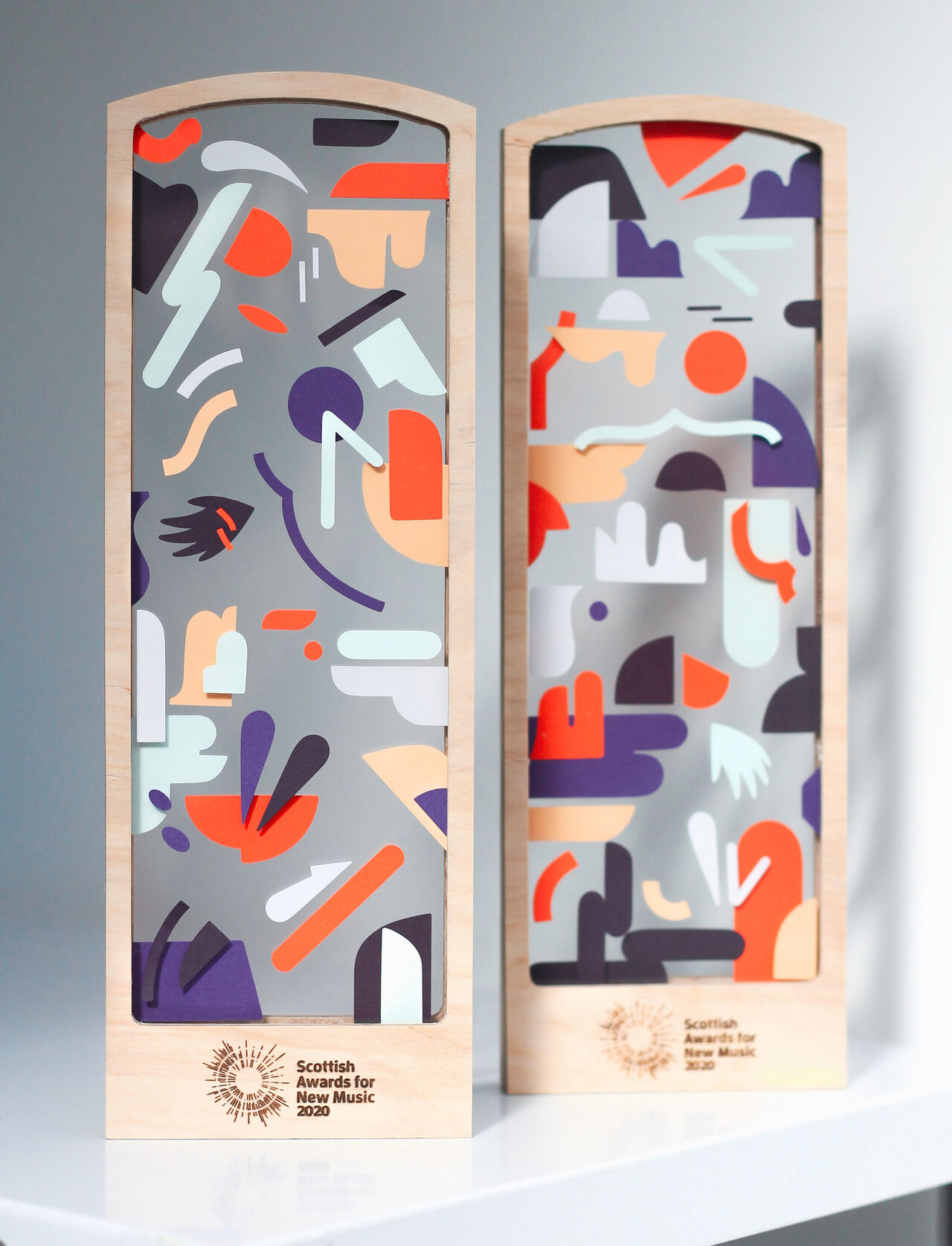 Two trophies made of wood with layers of glass between which are abstract colourful shapes of paper.