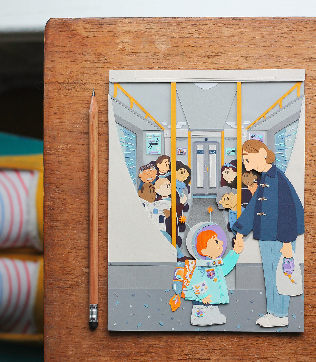 Top-down photo of an illustrated image of a child with their parent on the tube, entirely created out of cut out paper. A pencil lies next to it showing the intricate scale.