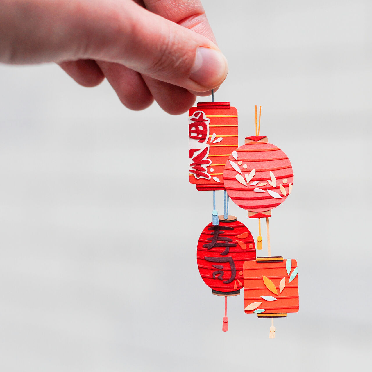 Photo of a hand holding tiny paper lanterns made out of intricate paper cuttings.