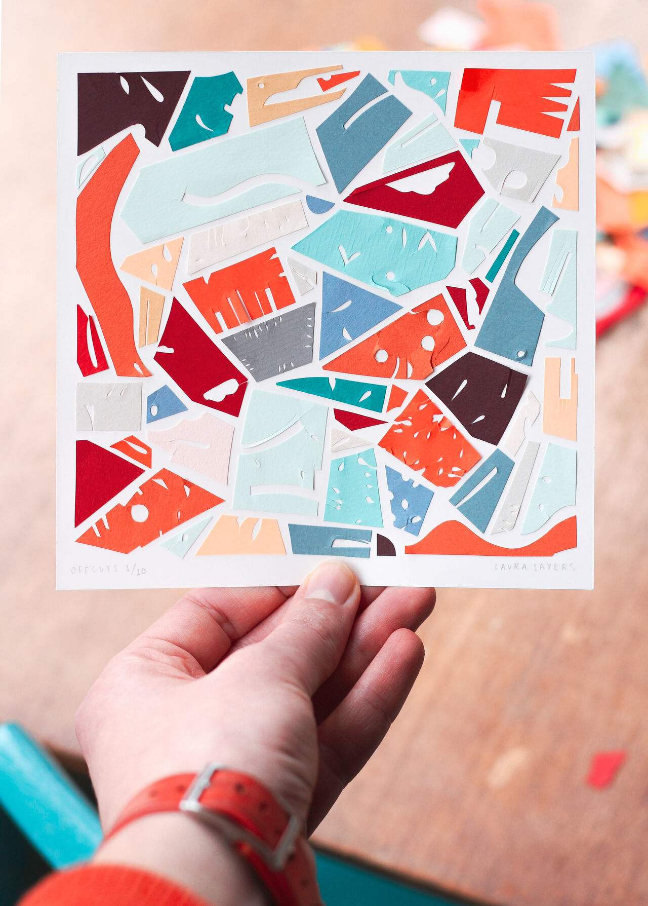 Photo of a hand holding a sheet of white paper on which are an amazing cluster of multi-coloured paper cut outs in abstract shapes and patterns.