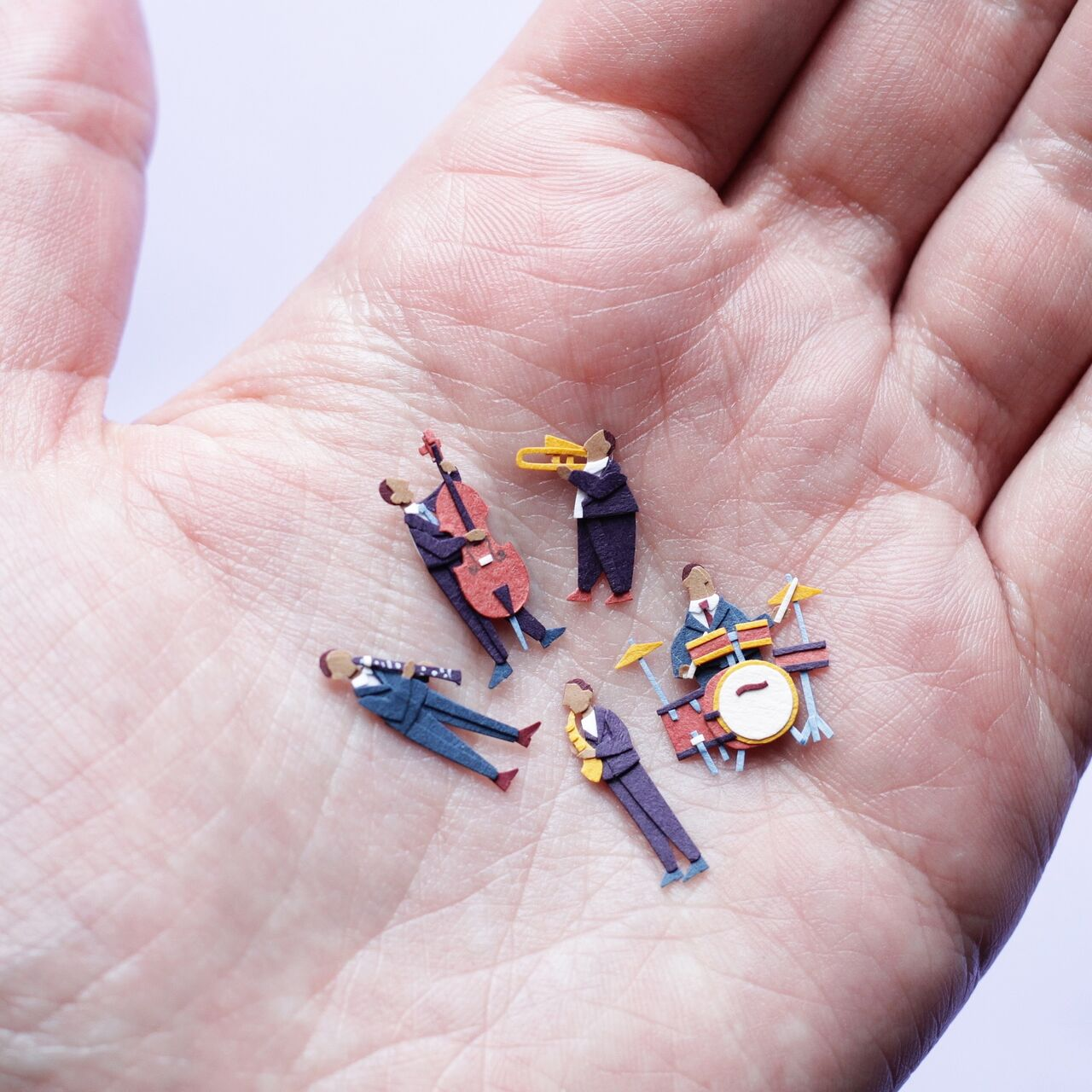 Photo of a hand holding tiny band members with instruments made out of intricate paper.