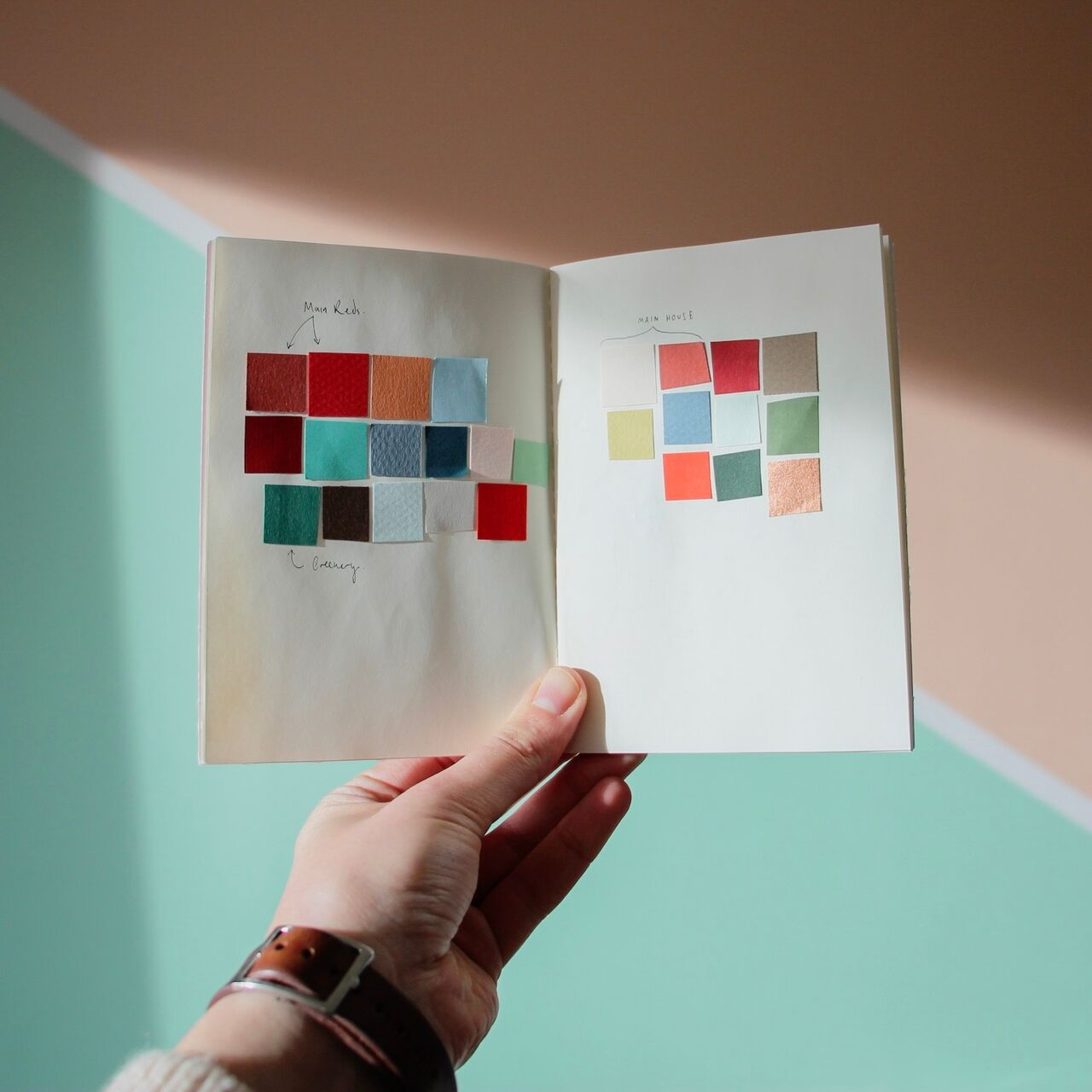 Photo of a sketchbook being held up and open by a hand. The sketchbook shows swatches of coloured card.