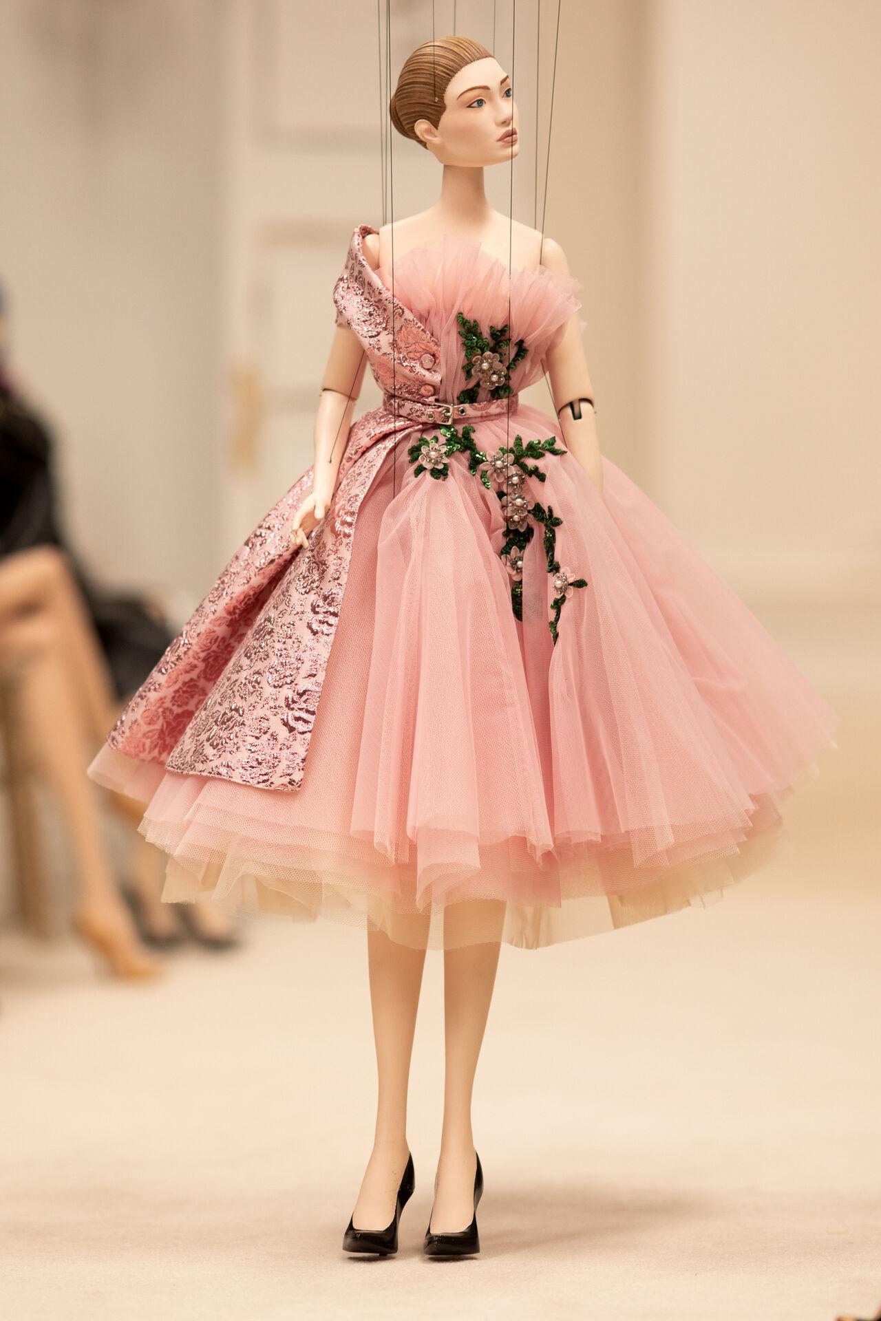 A puppet wearing a dress, walking down a runway.