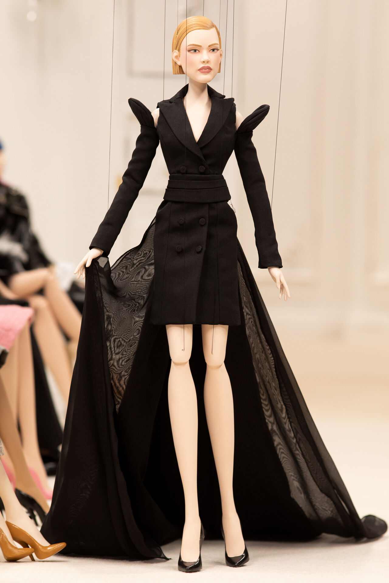 A puppet wearing a dress, walking down a runway.