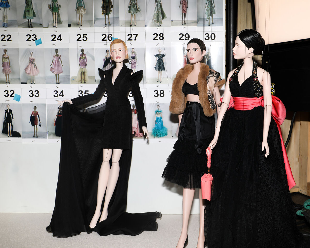 Three puppets wearing dresses, in the background you can see a wall showing outfits.