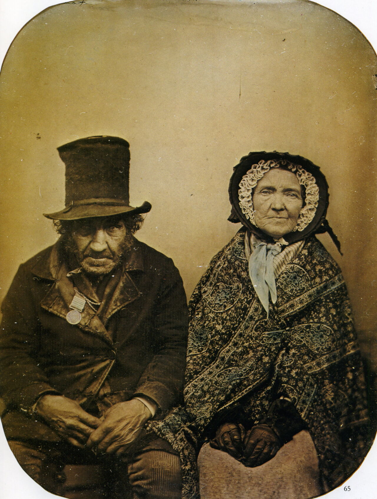 A male and female sitting next to each other, the woman is wrapped in a Paisley shawl.