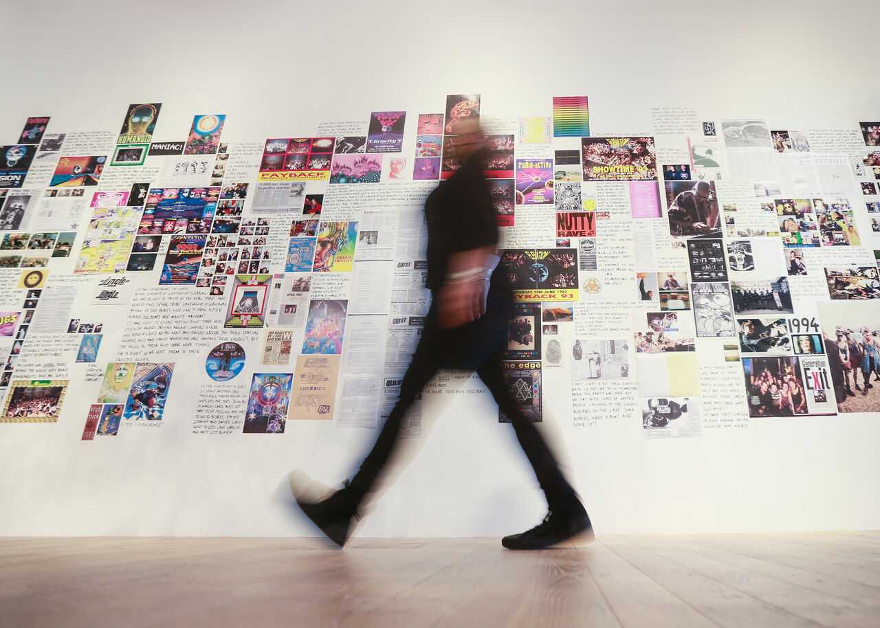 A wall with several images and posters, someone is walking in front of the wall.