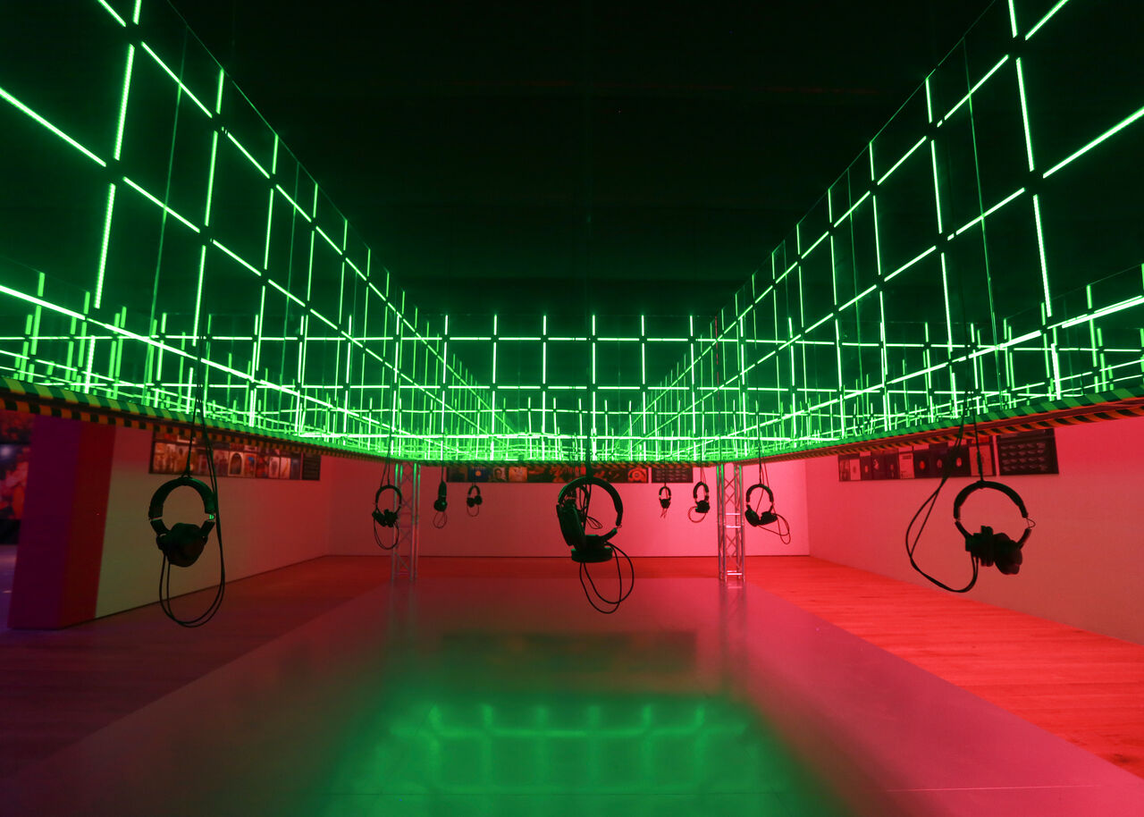 A silent disco which is covered by a large frame with mirrors and lights inside, headphones are hanging from the roof.