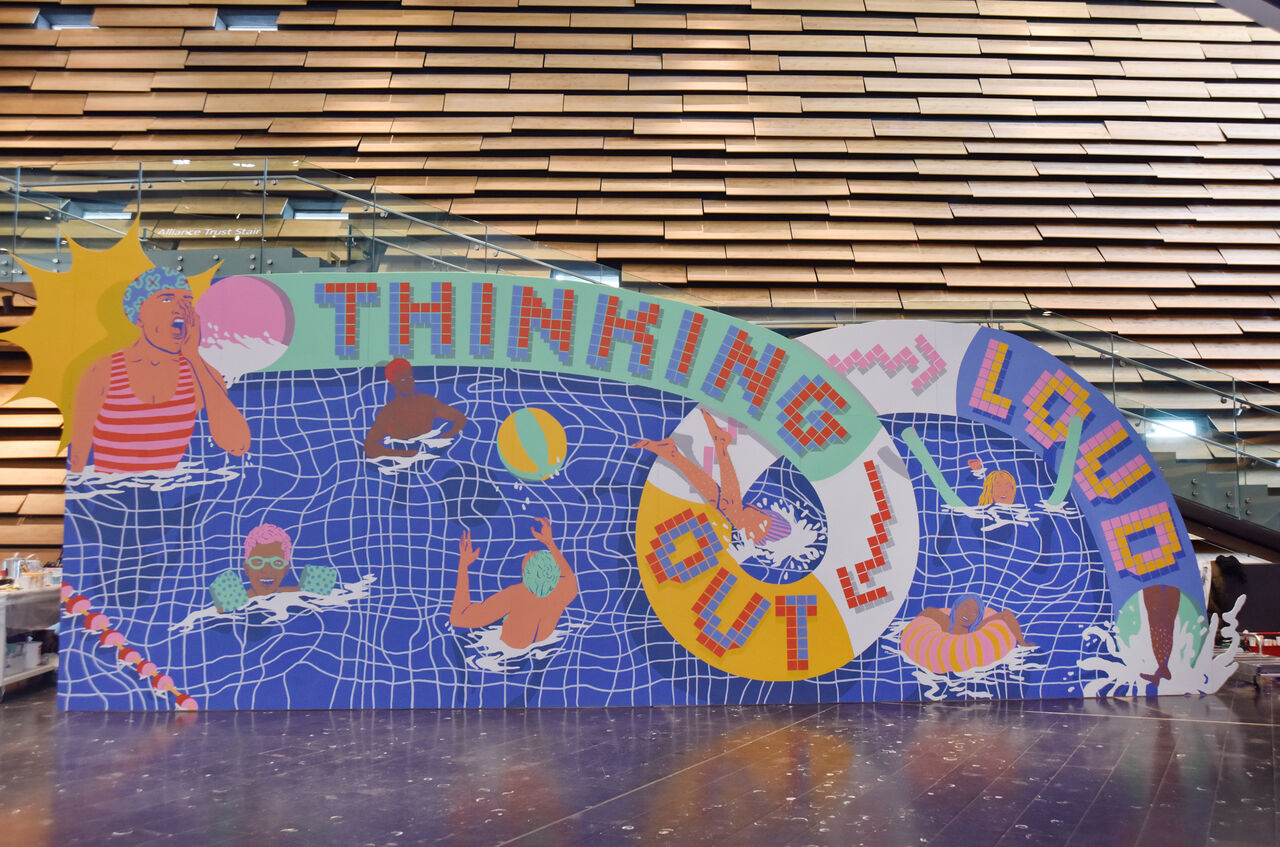 A large mural which depicts a swimming pool, you can see people throwing balls in the pool and the words 'Thinking Out Loud' can be seen at the top.
