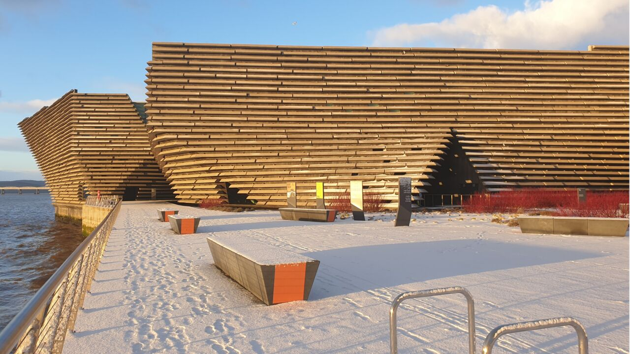 A wide shot of V&A Dundee, snow is covered the ground, seating and building.
