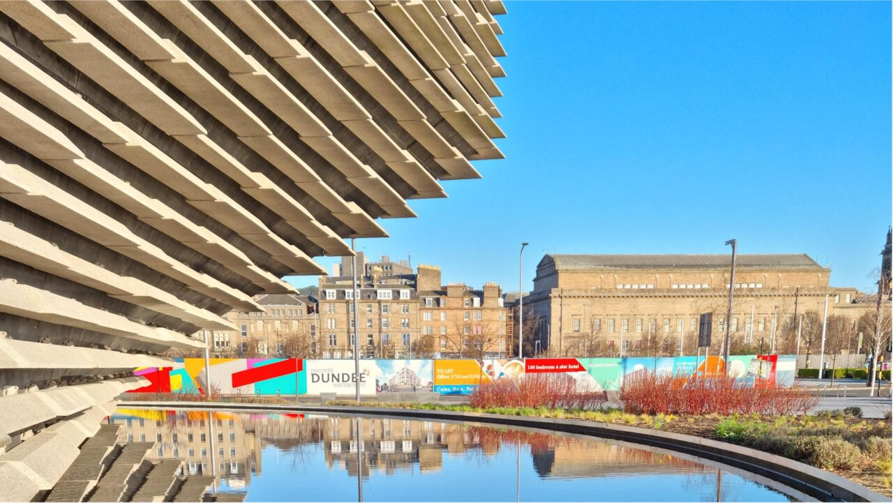 An image of V&A Dundee, in the background buildings can be seen and their reflections in the water surrounding the museum.